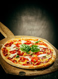 Fresh Baked Pizza Served on Wooden Pizza Paddle Royalty Free Stock Photos