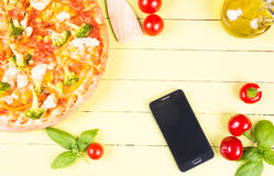 Pizza and phone on wooden table Royalty Free Stock Images