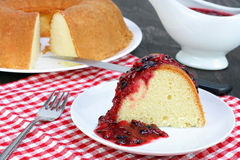 Fresh baked pound bundt cake with fruit sauce. Freshly baked bundt pound cake with a delicious mixed berry fruit sauce Royalty Free Stock Images