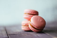 Fresh baked purple pink macaroon pastry cookies macarons, macaroni in retail store display, close up, low angle view stock photo