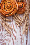 Fresh-baked raisin buns wheat ears on vintage. Wooden board food and drink concept Stock Images