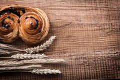 Fresh-baked raisin roll heap of wheat ears on oak Royalty Free Stock Photo