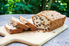 Fresh baked sliced raisin bread on wooden table. Fresh baked sliced raisin bread on a cutting board on wooden table in summer Royalty Free Stock Image