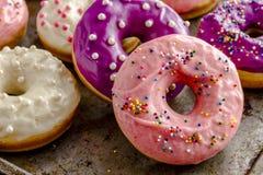 Fresh Baked Vanilla Bean Iced Doughnuts. Close up of homemade vanilla bean donut with pink icing sitting on metal baking pan Stock Photo