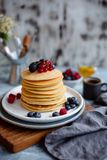 Wheat pancakes with berries on a wooden vintage board. Morning light in royalty free stock image