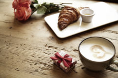 Fresh bakery croissant, coffee with heart sign, rose flowers on wooden table. Romantic breakfast for Valentine`s Day celebrate con Stock Image