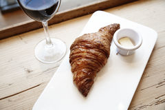 Fresh bakery croissant and glass of red wine in wooden table. City cafe daylight near window Royalty Free Stock Photos
