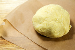 Fresh ball of shortcrust dough on baking paper, ready to roll it Royalty Free Stock Photos