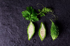 Fresh Balsam Pear on wet black stone plate background Stock Photos
