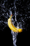 Fresh banana gets hit by a water stream Royalty Free Stock Images