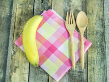 Fresh banana, spoon and fork in napkin on wooden Stock Images
