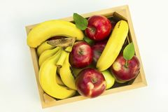 Fresh bananas and apples in box on white background. royalty free stock photo
