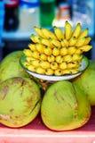 Fresh bananas and coconuts on a market. Fresh bananas and coconuts on a Balinese market Royalty Free Stock Photos