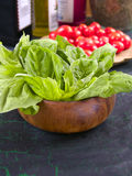 Fresh basil. In a wooden bowl with cherry tomatoes in the background Stock Photography