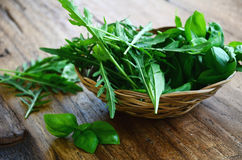 Fresh basil and arugula herbs in a wooden bowl Stock Photo