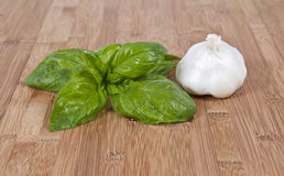 Fresh basil and garlic on bamboo board Stock Photos
