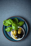 Fresh basil leaves with a bowl of olives Stock Photo
