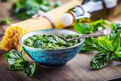 Fresh basil leaves pesto garlic and spaghetti on wooden table Stock Image