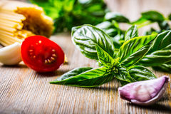 Fresh basil leaves tomatoes garlic an spaghetti on wooden table Royalty Free Stock Photography