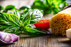 Fresh basil leaves tomatoes garlic an spaghetti on wooden table Stock Photo
