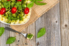 Fresh basil pesto dish with cherry tomatoes on rustic wood Royalty Free Stock Photos