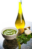 Fresh basil pesto. With olive oil container on granite counter top Stock Image