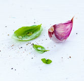 Fresh basil and purple garlic on white background. Bright modern composition Royalty Free Stock Photography