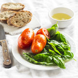 Fresh Basil, tomatoes on a white plate, olive oil and a baguette Stock Photography