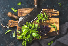 Fresh basil and vintage herb chopper on rustic wooden board Stock Photography