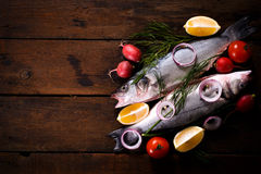 Fresh bass fish on wooden background. Fresh bass fish on the wooden background with blank space,selective focus Royalty Free Stock Images