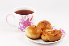 Fresh batch with a cup of tea. Fresh batch on a plate and a cup of tea on a white background stock photo