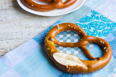 Fresh Bavarian pretzel on blue towel. National Bavarian pastry - crunchy pretzel Royalty Free Stock Image