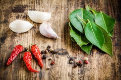 Fresh bay leaves, garlic cloves, red chili pepper on a wooden background Royalty Free Stock Photo