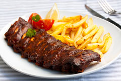 Fresh BBQ, marinated spareribs and fries royalty free stock images