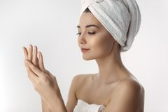 Fresh and Beautiful brunette woman applying hands cream royalty free stock photos