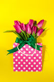 Fresh beautiful lila tulips in gift package on bright yellow bac Royalty Free Stock Image