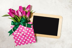 Fresh beautiful lila tulips in gift package on marble background Stock Photo