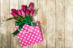 Fresh beautiful lila tulips in gift package on wooden background Royalty Free Stock Image