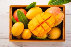 Fresh and beautiful mango fruit set in a wooden box with sliced diced mango chunks on a light wooden background,. Copy spacetext space, blank for text Stock Images