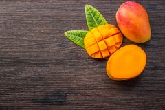 Fresh and beautiful mango fruit with sliced diced mango chunks on a dark wooden background, copy spacetext space, blank for text. Top view stock images