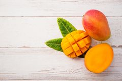 Fresh and beautiful mango fruit with sliced diced mango chunks on a light wooden background, copy spacetext space. Blank for text, top view royalty free stock images