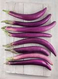 Fresh, beautiful purple violet eggplants decorated on a white wood table, studio shoot. Can be used as background Stock Photos