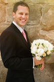 Fresh beautiful white roses wedding bouquet in handsome groom ha. Nds Stock Photo