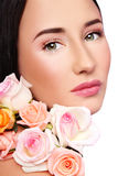 Fresh beauty. Close-up portrait of young beautiful woman with clear make-up and fresh tender roses Royalty Free Stock Image