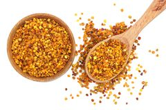 Fresh bee pollen in wooden spoon and bowl isolated on white background. Top view. Flat lay.  royalty free stock images