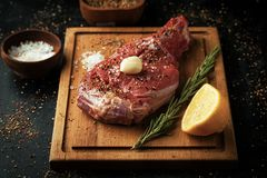 Fresh beef bone with salt, spices, rosemary and lemon on a woode. N board on a dark background Stock Image