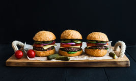 Fresh beef burgers on paper over rustic wooden tray, black background. Stock Photo