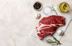 Fresh beef meat on white background with olive oil, herbs and spices royalty free stock photos