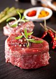Fresh beef raw steaks on black stone. Pieces of red raw meat steaks with rosemary served on black stone surface Stock Image