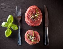 Fresh beef raw steaks on black stone. Pieces of red raw meat steaks with herbs, served on black stone surface. Shot from upper view Stock Photography